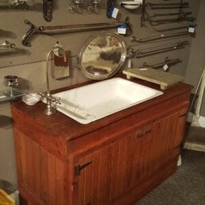 Porcelain sink in a primitive wooden cabinet.