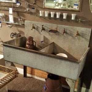 Double basin galvanized sink with straight legs and tall back splash.